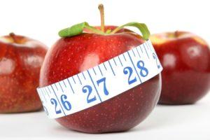 Apfel mit Maßband symbolsiert ein gesundes Abnehmen